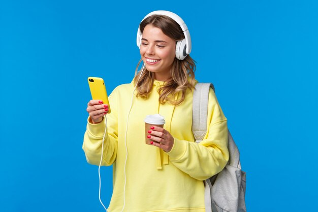 Beztroska uśmiechnięta blond kobieta w żółtej bluzie z kapturem słuchająca muzyki w słuchawkach, wybierająca piosenkę z listy odtwarzania jako pijąca kawę w drodze do domu z uniwersytetu, trzymaj plecak, niebieska ściana