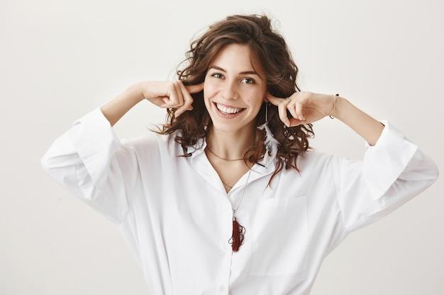 Beztroska uśmiechnięta kobieta zamykająca uszy