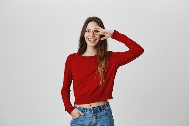 Beztroska uśmiechnięta, szczęśliwa kobieta nie ma problemu z podpisaniem oka
