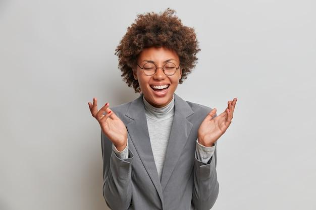 Beztroska, uszczęśliwiona pracownica biura śmieje się radośnie, rozbawiona zabawnymi kolegami, zamyka oczy ze szczęścia, nosi formalne ubrania, słyszy zabawną historię, ma optymistyczny nastrój