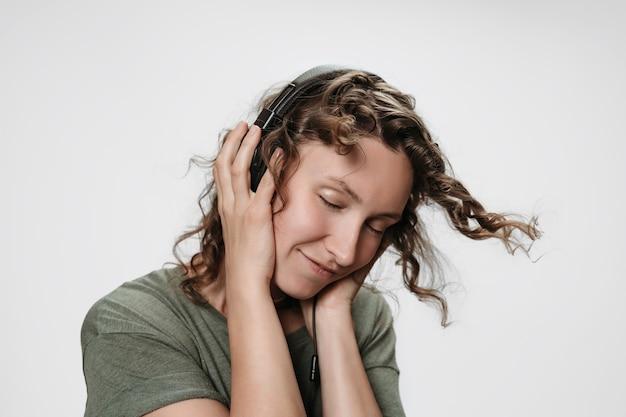 Beztroska, wesoła, młoda, kręcona kobieta słucha ulubionej muzyki z ręką na słuchawkach