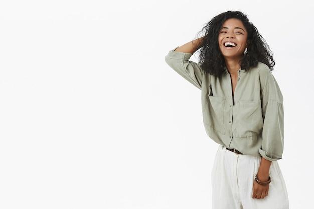 Beztroska zachwycona i szczęśliwa kreatywna afroamerykanin kobieta w modnej koszuli i spodniach, trzymając rękę na włosach