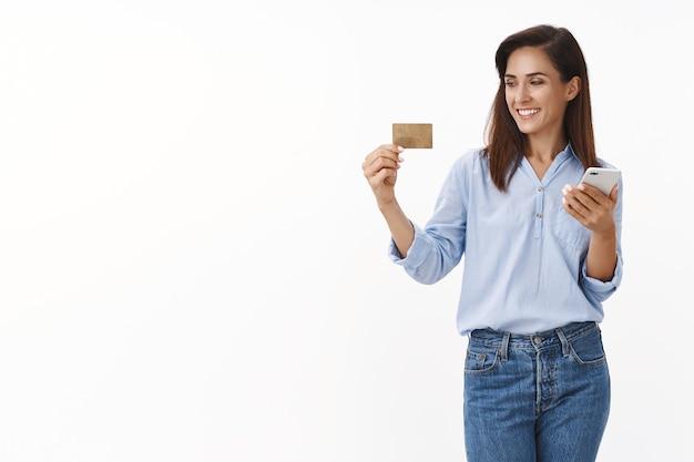 Beztroska zrelaksowana dorosła kobieta wprowadź numer karty kredytowej zamów ubrania online, zakupy w aplikacji internetowej, spójrz cvv uśmiechnięty zadowolony, trzymaj stojak na smartfona biała ściana