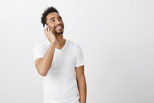 Beztroski afroamerykanin patrząc w prawym górnym rogu z radosnym uśmiechem podczas rozmowy przez telefon komórkowy