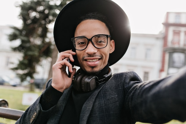 Beztroski afrykański facet w okularach co selfie w parku. odkryty zdjęcie mulata mężczyzny w modnym stroju, robienia sobie zdjęcia.