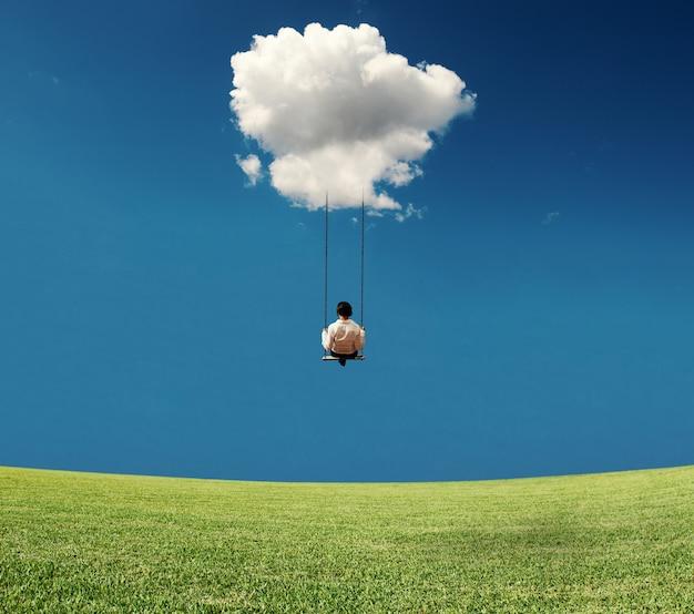 Beztroski bizneswoman na huśtawce przyczepiony w chmurze