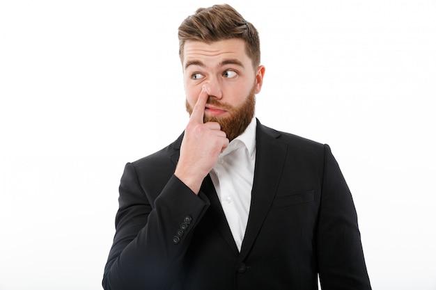 Beztroski brodaty mężczyzna trzyma palec w nosie