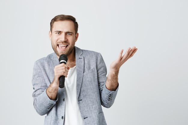 Beztroski brodaty wykonawca śpiewający piosenkę do mikrofonu