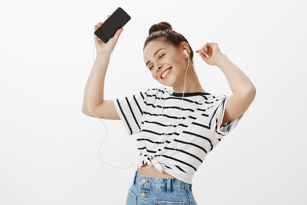 Beztroski całkiem kaukaski dziewczyna tańczy w słuchawkach ze smartfonem