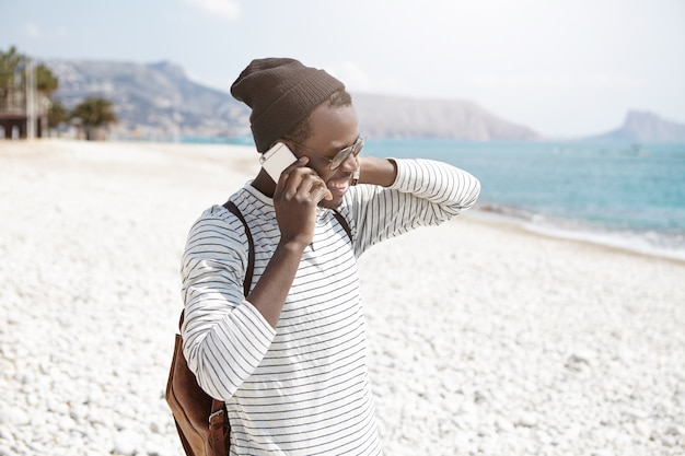 Beztroski ciemnoskóry hipster w modnych ubraniach, rozmawiając na smartfonie podczas spaceru po kamienistej plaży, relaksując się w letni dzień nad morzem