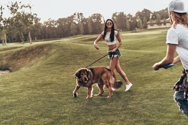 Beztroski czas razem. pełna długość pięknej młodej pary bawiącej się z psem podczas spędzania czasu na świeżym powietrzu
