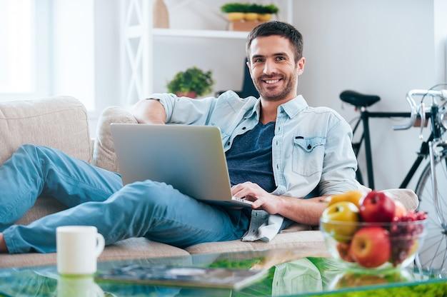 Beztroski czas w domu. przystojny młody mężczyzna pracujący na laptopie i uśmiechający się leżąc na kanapie w domu