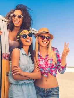 Beztroski czas z przyjaciółmi. szczęśliwa młoda afrykańska kobieta wygląda z retro minivana, podczas gdy dwóch jej przyjaciół stoi obok niej