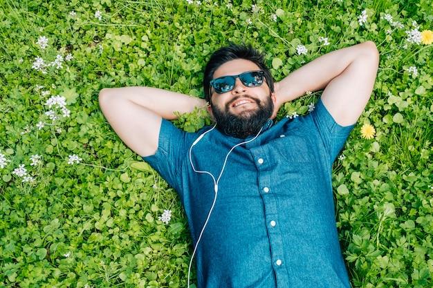 Beztroski człowiek leżący na trawie i słuchania muzyki