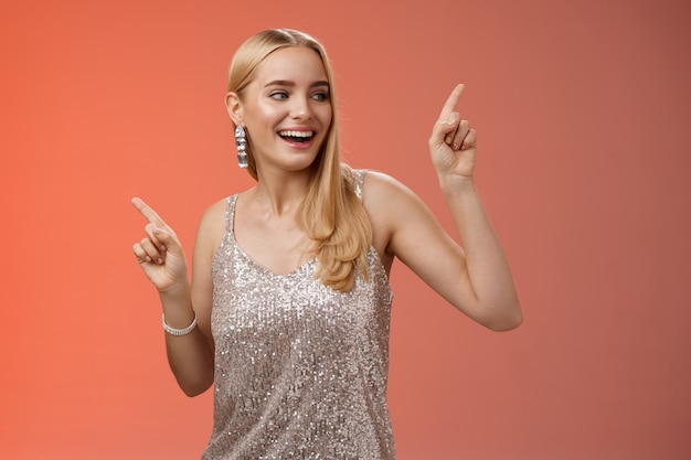 Beztroski elegancki radosny uroczy blond dziewczyna tańczy chłopak party klub nocny stojący na czerwonym tle w srebrnej błyszczącej sukience podnosząc ręce w górę w rytm muzyki ciała, uśmiechając się.