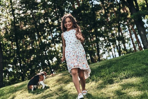 Beztroski i szczęśliwy. pełna długość uroczej małej dziewczynki bawiącej się z psem i uśmiechającej się podczas spaceru na świeżym powietrzu