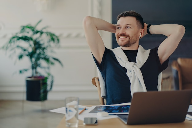 Beztroski męski przedsiębiorca lub wolny strzelec gotowy do pracy siedząc w swoim przytulnym miejscu pracy w domu z laptopem i dokumentacją projektową. mężczyzna trzymający ręce za głową i patrzący na bok