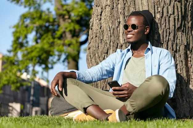 Beztroski mężczyzna o ciemnej skórze i białych doskonałych zębach, ubrany w modne ciuchy, siedzący na zielonej trawie w parku, oparty o drzewo, trzymający w dłoni telefon komórkowy, odbierający wiadomości od dziewczyny