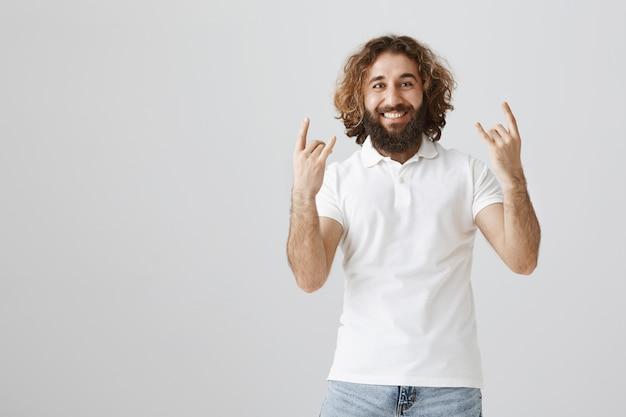 Beztroski mężczyzna z bliskiego wschodu pokazujący rock-n-rollowy gest, bawiący się