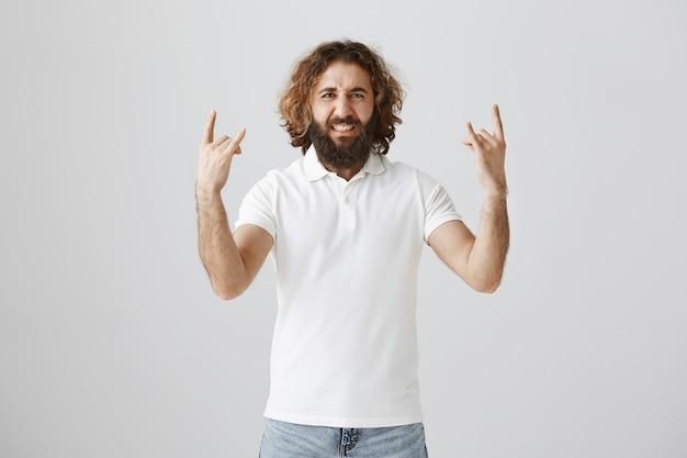 Beztroski mężczyzna z bliskiego wschodu pokazujący rock-n-rollowy gest