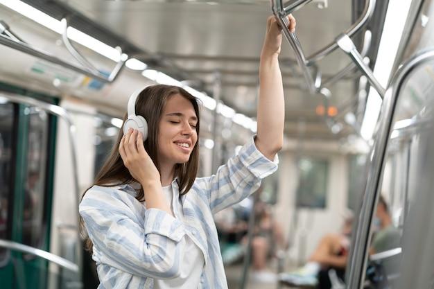 Beztroski milenijny pasażer słodkiej dziewczyny słuchający muzyki za pomocą bezprzewodowych słuchawek w pociągu metra