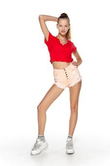 Beztroski. piękna, młoda dziewczyna w stylowy strój na białym tle na tle białego studia. styl magazynu, moda, koncepcja piękna. modne pozowanie. copyspace dla reklamy.
