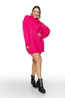 Beztroski. piękna młoda kobieta jasny różowy wygodny sweter, długi rękaw na białym tle