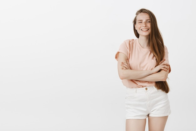Beztroski piękna nastolatka pozuje na białej ścianie