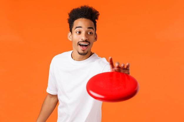 Beztroski przyjazny i szczęśliwy uśmiechnięty młody nowoczesny mężczyzna afroamerykanów w białej koszulce