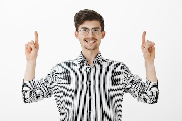 Beztroski, przyjazny student europejski z wąsami i brodą w modnych okrągłych okularach i koszuli w paski, unoszący palce wskazujące i wskazujący w górę, uśmiechając się szeroko, mówiąc, że znalazł świetne miejsce