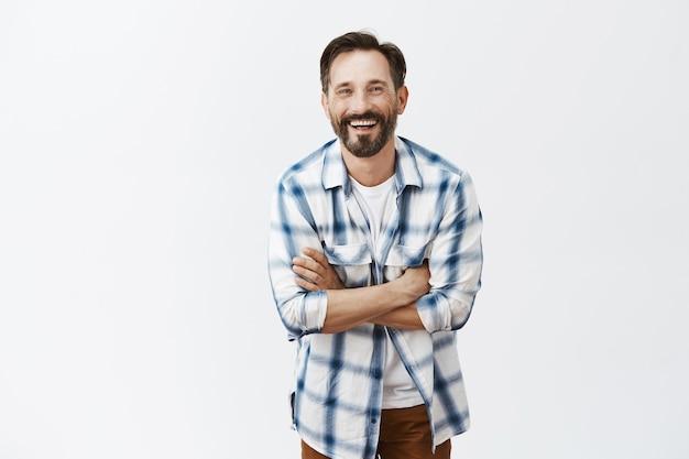 Beztroski przystojny brodaty dojrzały mężczyzna śmiejąc się i uśmiechając