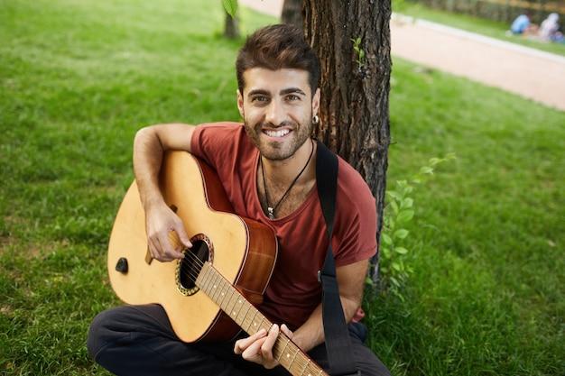 Beztroski przystojny facet gra na gitarze w parku