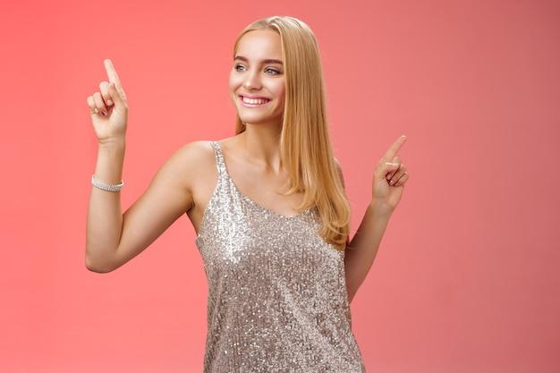 Beztroski przystojny stylowy glamour blond młoda 20s kobieta w srebrnej błyszczącej sukience taniec zabawy rozbawiony szaleństwo impreza noc balu drżenie ciała podnoszenie palców wskazujących w górę, czerwone tło