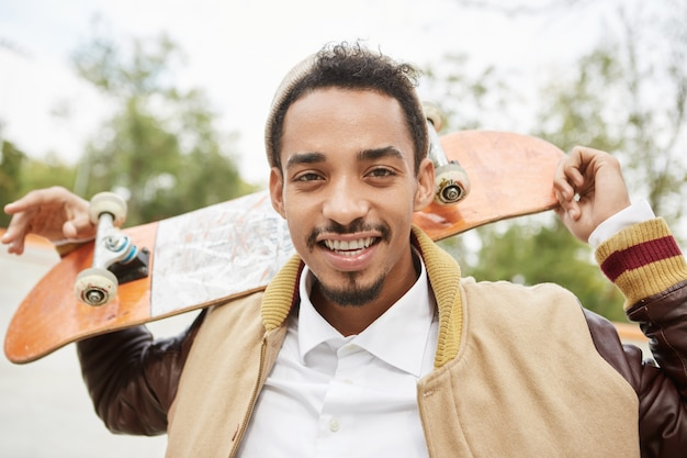 Beztroski sketaboarder rasy mieszanej trzyma za sobą deskorolkę, uśmiecha się radośnie