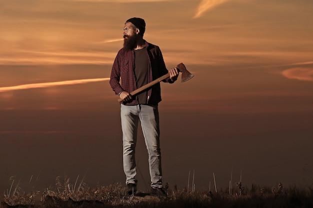 Beztroski szczęście koncepcja wolności hipster mężczyzna z brodą z siekierą w dłoni i wąsami w kapeluszu skacze z siekierą na szczycie góry na pochmurnym niebie
