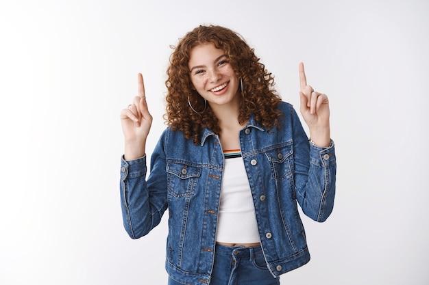 Beztroski szczęśliwa czarująca uśmiechnięta europejka ruda dziewczyna piegi skóra potrądzikowa śmiejąca się radośnie podnoszenie dłoni wskazujące palce wskazujące w górę promocja produktu reklama stojąca zachwycona optymistyczna biała ściana