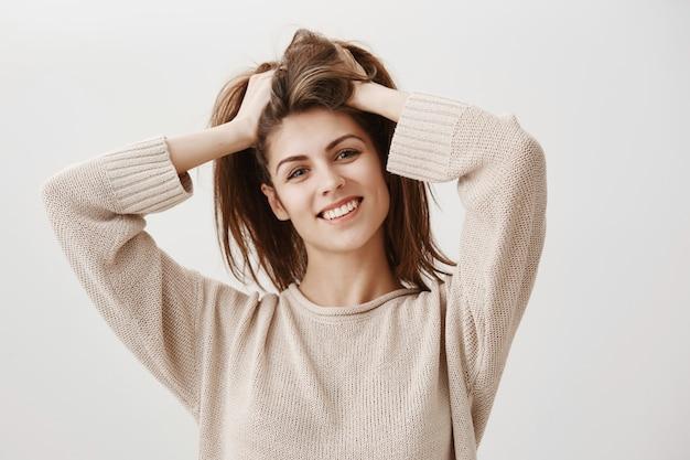 Beztroski szczęśliwa kobieta uśmiecha się do podrzucania włosów