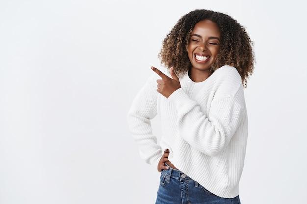 Beztroski szczęśliwy ciemnoskóry pulchny młoda kobieta kręcone fryzury nosić sweter trzymać kieszeń za rękę beztroski radosny uśmiechnięty śmiech radośnie wskazujący lewy górny róg zabawny promo, zabawna reklama