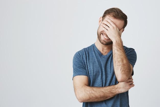 Beztroski, szczęśliwy facet śmieje się z żartu, chichocze i zamyka oczy