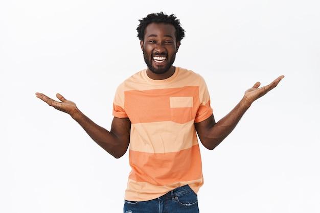 Beztroski, szczęśliwy, wzruszający młody, entuzjastyczny afroamerykanin z brodą, fryzurą afro