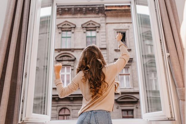 Beztroski, szczupła dziewczyna w dżinsach, taniec obok okna z filiżanką kawy