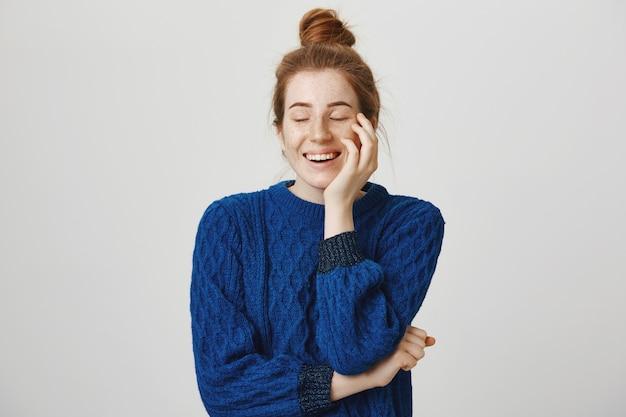 Beztroski uśmiechnięta i wesoła ruda kobieta śmiejąca się