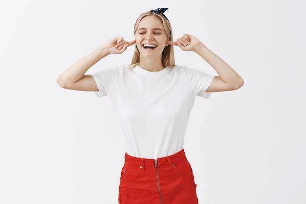 Beztroski uśmiechnięta młoda blond dziewczyna pozuje na białej ścianie