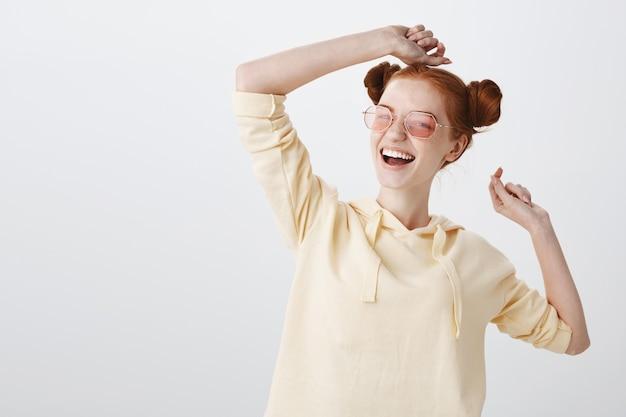 Beztroski uśmiechnięta ruda dziewczyna w okularach przeciwsłonecznych, ciesząc się latem