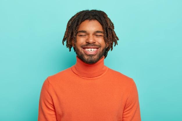 Beztroski uśmiechnięty facet ma wesoły wyraz twarzy, śmieje się z czegoś pozytywnego, pokazuje białe zęby, nosi pomarańczowy poloneck