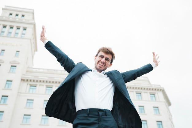 Beztroski uśmiechnięty młody biznesmen stoi przed budynkiem podnosi jego ręki