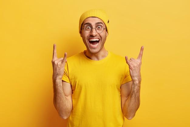 Beztroski uśmiechnięty pozytywny mężczyzna wykonuje rock n rollowy gest, lubi fajną muzykę, radośnie lauhg