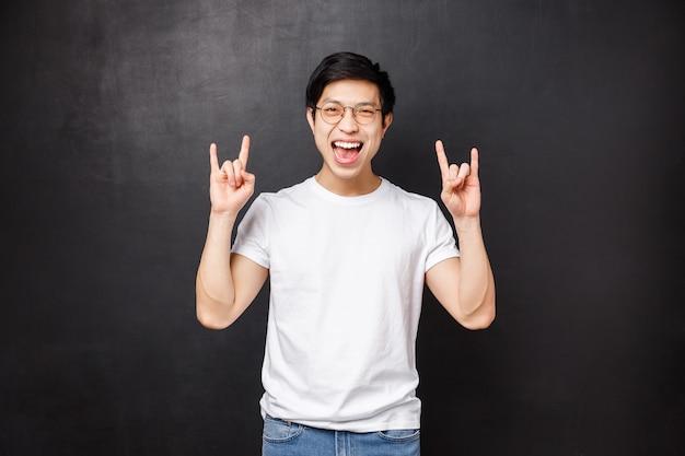 Beztroski wychodzący młody student dobrze się bawi na niesamowitej imprezie w akademiku, słuchając fajnej muzyki na festiwalu, wykonuj gest rock-n-roll uśmiechając się i tańcząc, stojąc