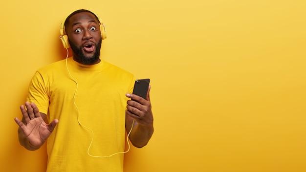 Beztroski zaskoczony szczęśliwy mężczyzna ma ciemną skórę, grube włosie, słucha muzyki w słuchawkach, trzyma nowoczesny smartfon