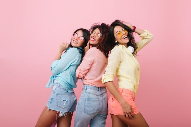 Beztroskie dziewczyny w kolorowych bawełnianych koszulach pozują razem i uśmiechają się. kryty portret atrakcyjnych młodych kobiet wyrażających szczęśliwe emocje.